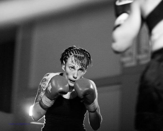 Emily Jans exhibiting boxing form, raising her arms in anticipation to strike