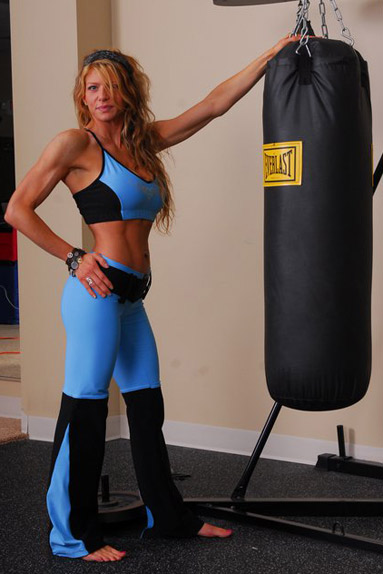 Award-winning vegan bodybuilder, Amanda Reister, poses next to a punching-bag