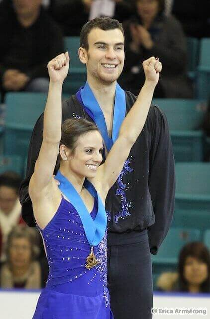 Meagan Duhamel raises both arms in victory alongside her partner