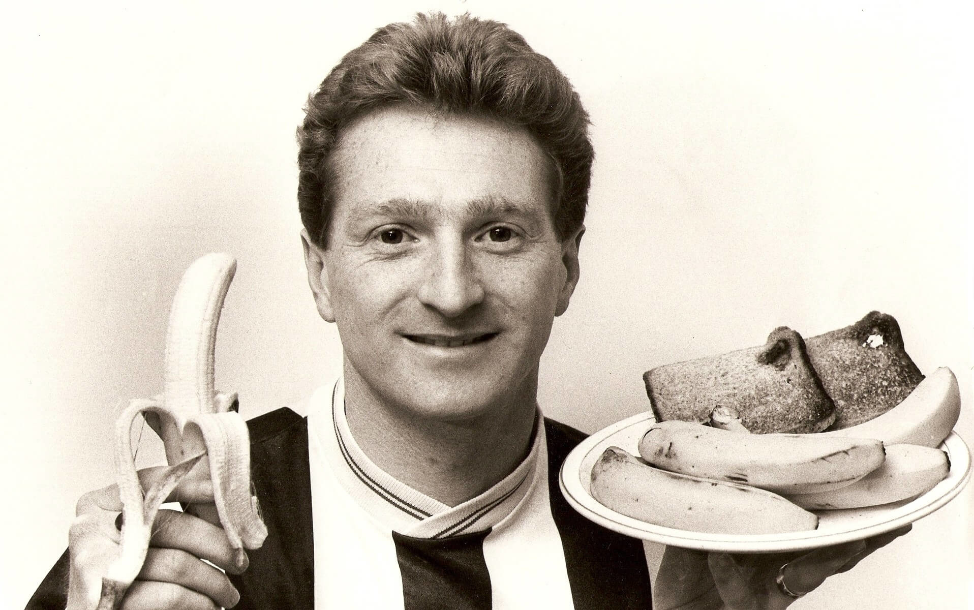 Neil Robinson with a banana in one hand and a plate in the other